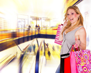 Happy blond woman with shopping bags in shopping center