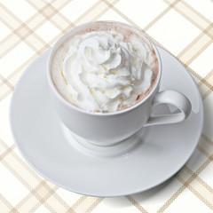 Tasse Kakao mit Sahnehäubchen auf Karodecke