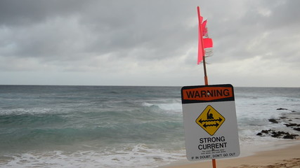 A warning sign at a stormy beach
