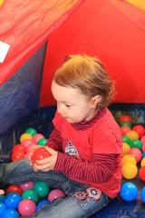 Spielendes Kind im Bällchenbad