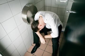 Junger betrunkener Mann schläft auf Toilette