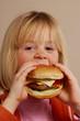 Niña feliz comiendo hamburguesa,comida rápida.