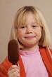 Niña comiendo una paleta de helado de chocolate.