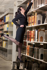 Sexy librarian reaching for a book high on a shelf.