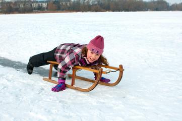 Mädchen mit dem Schlitten auf dem Eis