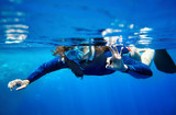 Scuba diver woman in  blue water.