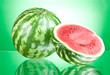Watermelon and half on a green background