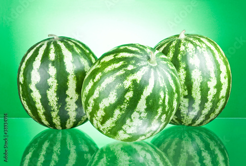 Three Watermelons isolated on a green background