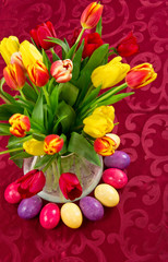 Easter concept with tulips and colored eggs