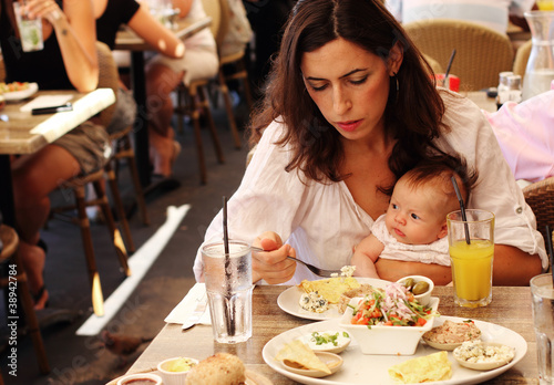 young mother with her daughter in a cafe eating breakfast