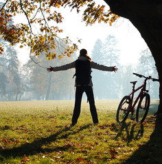 Excited woman cyclist standing in a park with hands outstretched