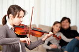 young girl playing violin with her family at home