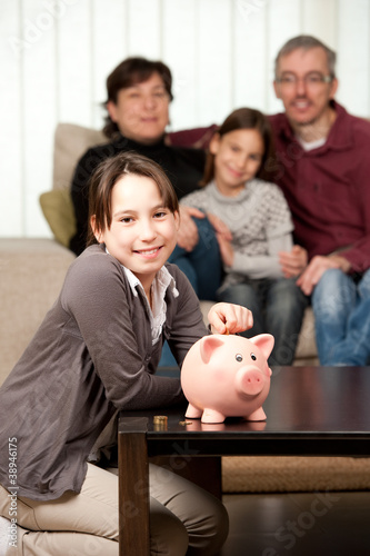 young girl  with her parents saving money on a piggy bank