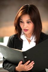 Portrait of businesswoman of Asian holding black file document .