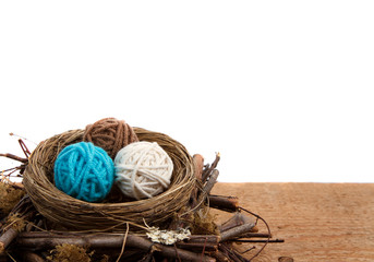 Balls of yarn in a nest, white background