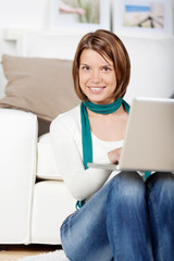 junge frau mit laptop vor dem sofa