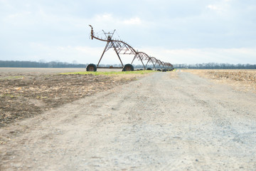 Mobile irrigation system lining a dirt road in a field setting
