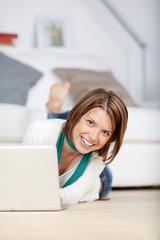 lächelnde junge frau mit laptop zu hause