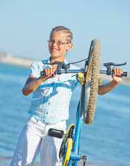 beautiful young girl standing with her bicycle