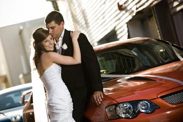 Newlyweds embracing against a wedding car