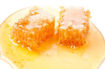 Close-up of fresh honey and slices of honeycomb, studio shot