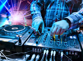 Dj mixes the track in the nightclub
