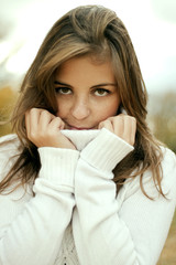 Portrait of the beautiful and young girl in a white sweater