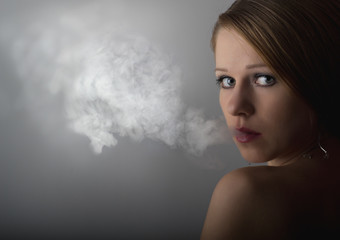 beautiful young woman with cigarette smoke on a dark gray backgr