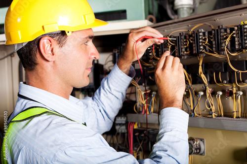 Leinwandbild Motiv male electrician testing industrial machine