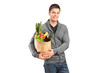 Smiling male holding a paper bag full of groceries
