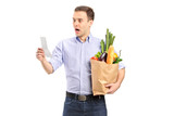 Surprised man looking at store receipt and holding a paper bag poster