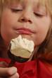 Niña comiendo una paleta de helado de chocolate y vainilla.