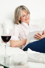 Seniorin liest Buch bei einem Glas Wein