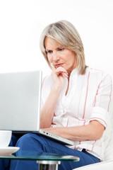 Seniorin schaut frustriert auf Laptop