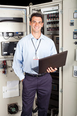 portrait of modern factory technician in front of machine
