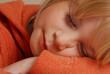 Retrato de una niña rubia descansando.