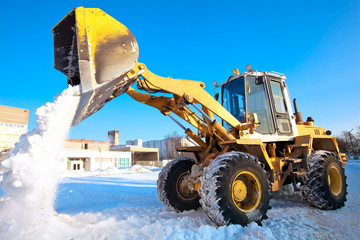 Wheel loader machine unloading snow during municipal works crews