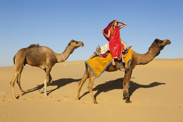 Woman in saree riding a camel Thar Desert, Rajasthan