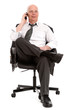 Älterer Geschäftsmann im Chefsessel telefoniert
