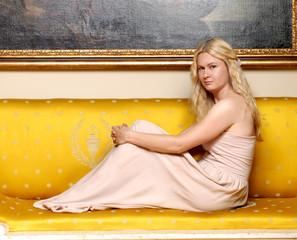 Mujer elegante sentada en un sofá.