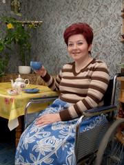 Женщина-инвалид пьет чай