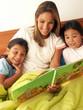 Madre leyendo un cuento a sus hijas en la cama.