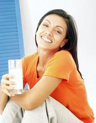 Joven mujer latina bebiendo leche.