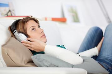 junge frau hört musik auf dem sofa