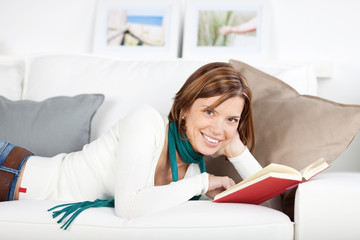 lächelnde frau liegt mit einem buch auf dem sofa