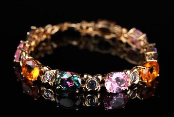 Beautiful bracelet with precious stones on black background