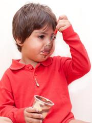 bambino che mangia cioccolato con il cucchiaino
