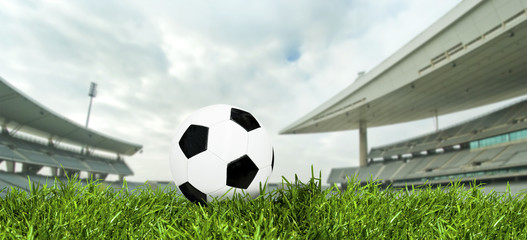 Classic soccer ball on green grass in a big stadium