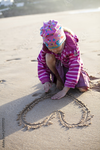 Girl drawing a heart in sand