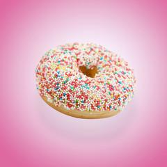 Donut mit bunten Zuckerperlen vor rosa Hintergrund